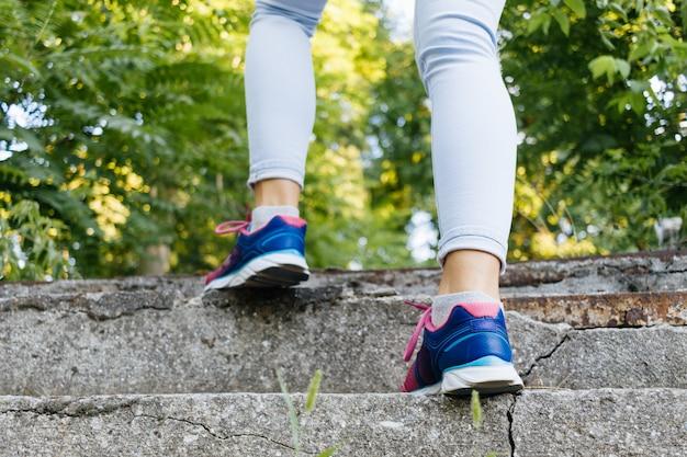 Le gambe femminili in scarpe da ginnastica e jeans salgono le scale di cemento nel parco