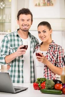 Le giovani belle coppie stanno bevendo il vino nella cucina.