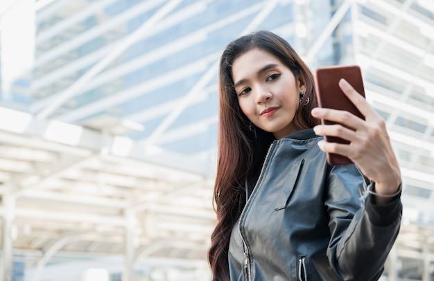 Le giovani belle donne asiatiche che per mezzo dello smartphone prendono un selfie.