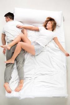Le giovani coppie adorabili che si trovano in un letto bianco, amano il lconcept, vista superiore