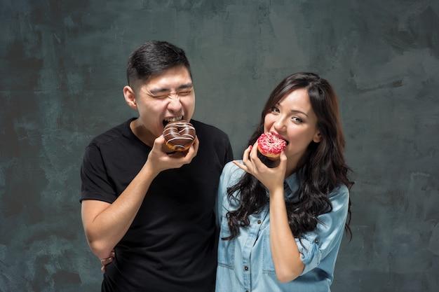 Le giovani coppie asiatiche amano mangiare della ciambella colorata dolce