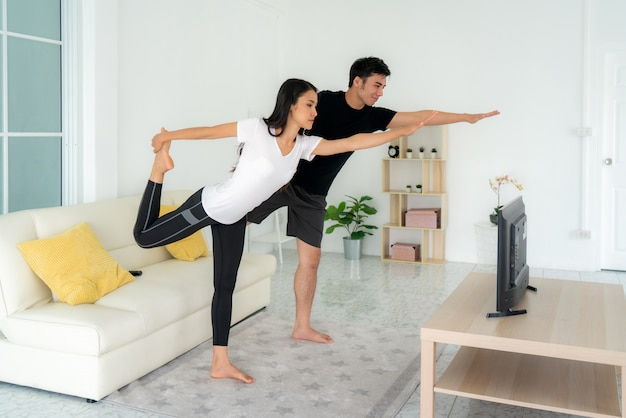 Le giovani coppie asiatiche che fanno l'yoga si esercitano insieme e che guardano la tv a casa