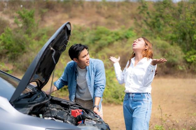 Le giovani coppie asiatiche con l'uomo e la donna sulla strada che hanno problemi ripartiscono il motore di automobile sulla strada e la donna che guardano lo sforzo quando un uomo non può riparare l'automobile.
