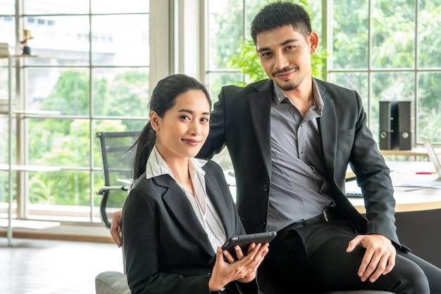 Le giovani coppie asiatiche del ritratto si siedono insieme sul sofà, concetto di affari