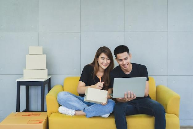 Le giovani coppie asiatiche felici del onwer della pmi di affari nell'abbigliamento casual con il fronte di smiley sta usando il computer portatile e stanno scrivendo il nome e l'indirizzo del cliente sulla scatola del pacchetto al loro ministero degli interni startup, venditore di consegna
