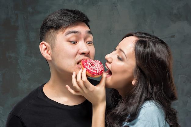 Le giovani coppie asiatiche godono di di mangiare la ciambella variopinta dolce
