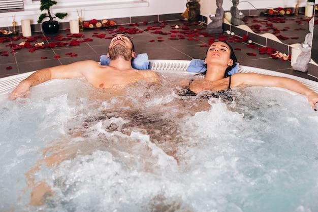 Le giovani coppie attraenti si rilassano in vasca calda