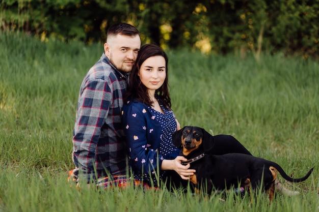 Le giovani coppie caucasiche felici si sono sedute sul prato inglese del parco con l'animale domestico del cane di salsiccia del cucciolo un giorno soleggiato
