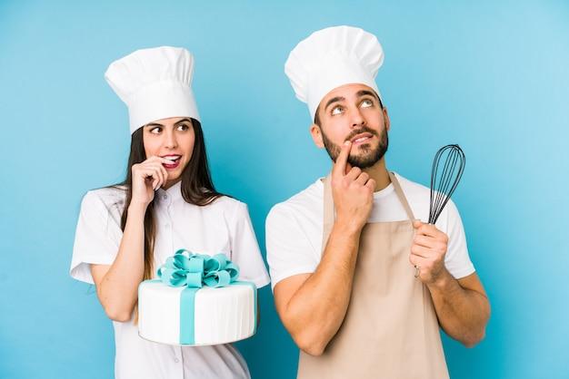 Le giovani coppie che cucinano una torta hanno isolato insieme il pensiero rilassato a qualcosa che esamina uno spazio della copia.