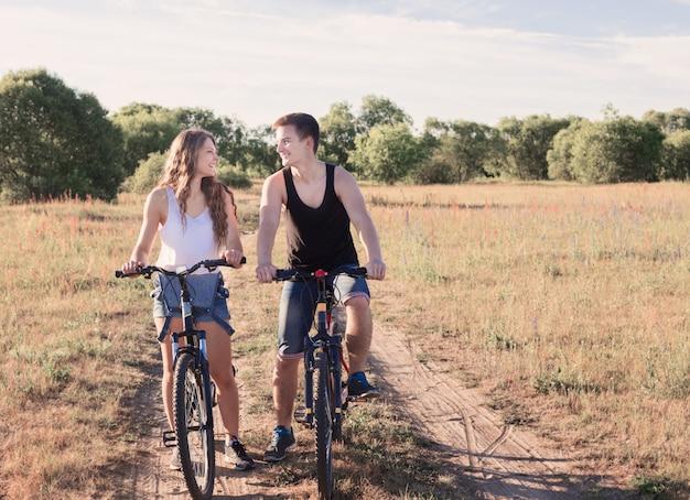 Le giovani coppie che hanno una bici guidano in natura
