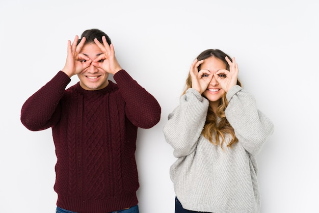 Le giovani coppie che posano in una parete bianca che mostra bene firmano sopra gli occhi