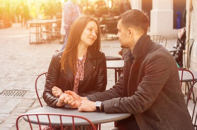 Le giovani coppie che si siedono al caffè della via al sole si svasano. appuntamento romantico