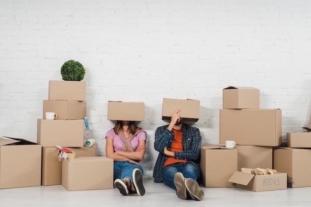 Le giovani coppie che si siedono sul pavimento con la loro testa hanno coperto di scatole di cartone nella loro nuova casa
