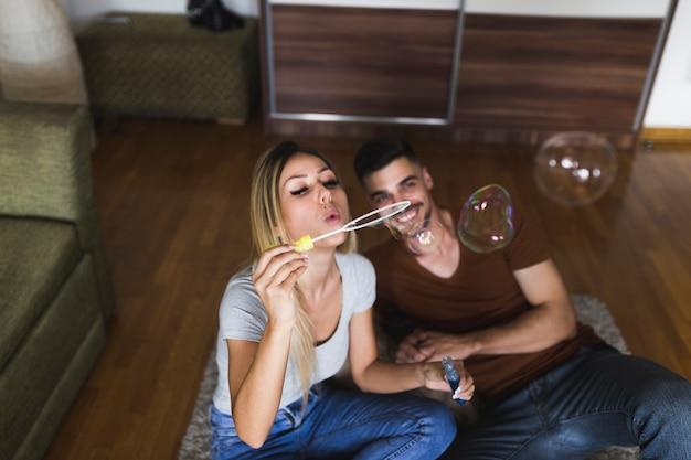 Le giovani coppie che si siedono sul pavimento di legno duro che soffia bolle con la bacchetta della bolla