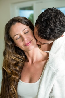 Le giovani coppie con gli occhi hanno chiuso l'abbraccio nel bagno e nel sorridere