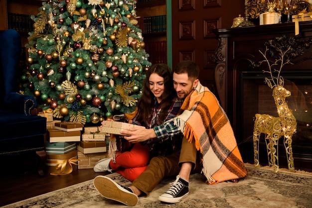 Le giovani coppie con i regali si avvicinano all'albero di natale