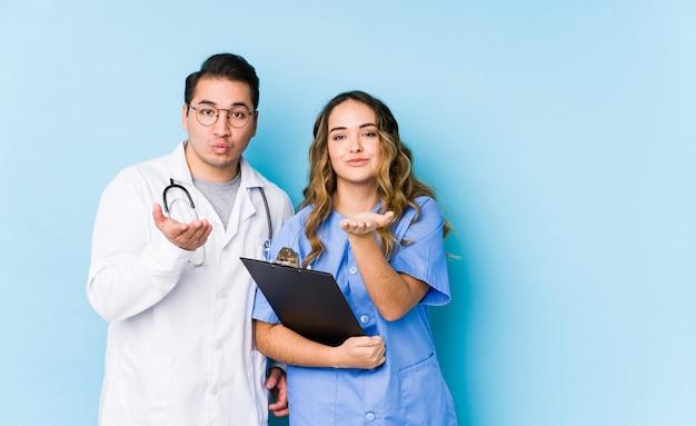 Le giovani coppie di medico che posano in una parete blu hanno isolato le labbra pieganti e la tenuta delle palme per inviare il bacio dell'aria.