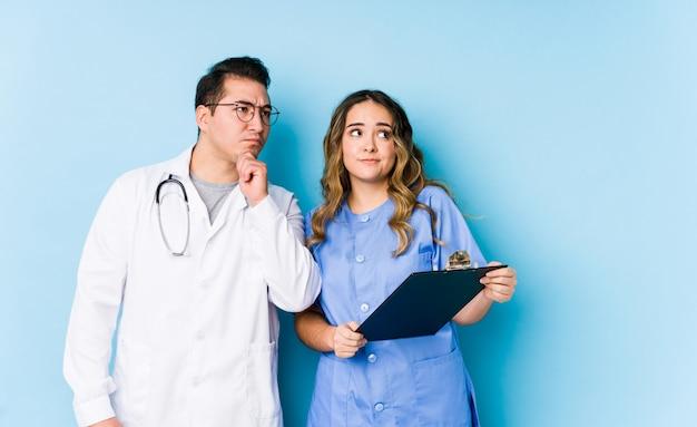 Le giovani coppie di medico che posano in una parete blu hanno isolato lo sguardo lateralmente con l'espressione dubbiosa e scettica.