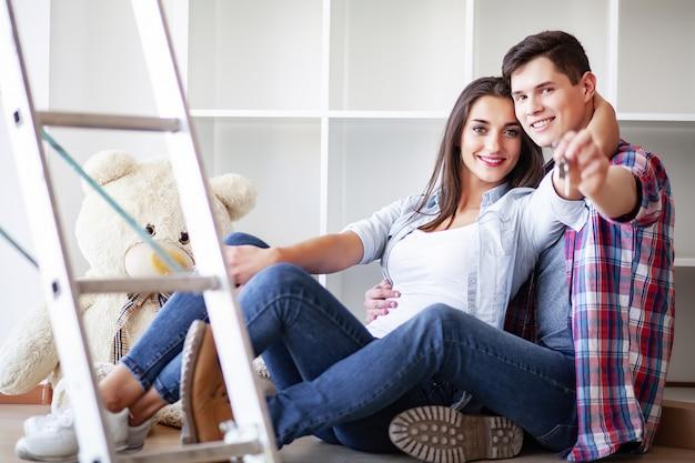 Le giovani coppie divertenti godono e celebrano il trasloco nella nuova casa. coppie felici a stanza vuota di nuova casa