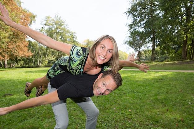Le giovani coppie felici che ridono e si divertono al parco della città