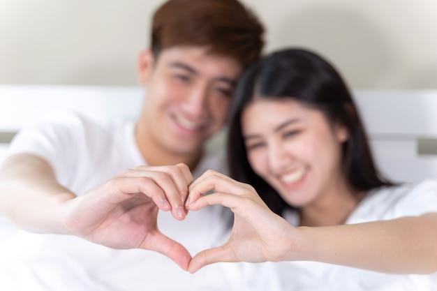 Le giovani coppie felici del ritratto che si siedono e che sorridono sul letto e sulla mano fanno insieme la forma del cuore