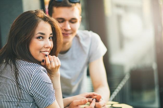 Le giovani coppie felici negli amici degli adolescenti di amore si sono vestite nello stile casuale che si siede insieme