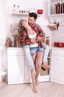 Le giovani coppie felici nell'amore stanno abbracciando e divertendosi nella cucina il giorno di san valentino di mattina. elegante uomo e donna con i capelli lunghi sono rilassanti a casa.