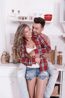 Le giovani coppie felici nell'amore stanno abbracciando e divertendosi nella cucina il giorno di san valentino di mattina. uomo e donna alla moda con capelli lunghi che si rilassano a casa