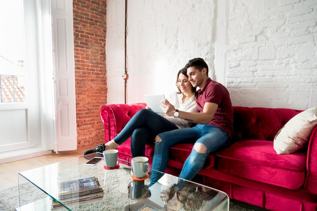 Le giovani coppie felici si sono distese nel paese con un tabet