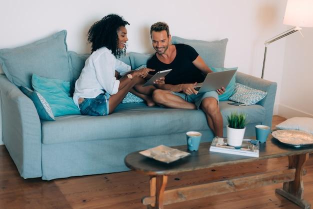 Le giovani coppie felici si sono rilassate a casa nello strato sul telefono cellulare e sul computer
