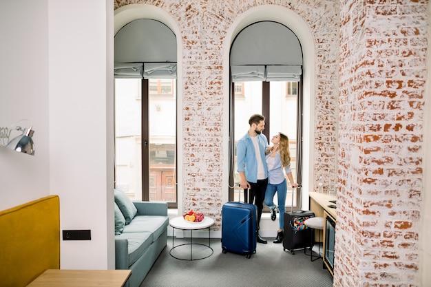 Le giovani coppie felici sono arrivate nella camera d'albergo in luna di miele o in viaggio d'affari.
