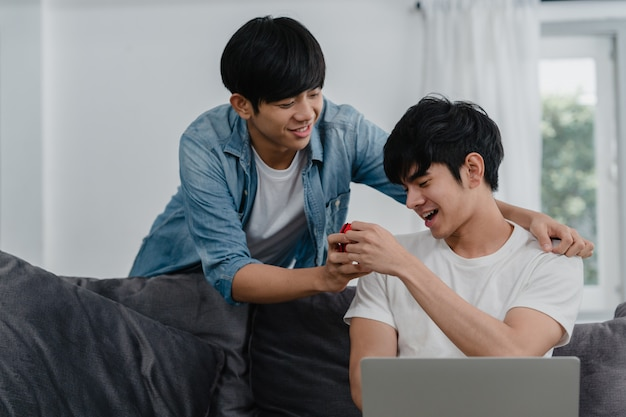 Le giovani coppie gay asiatiche propongono a casa moderna, gli uomini coreani adolescenti lgbtq che sorridono felici hanno tempo romantico mentre propongono e la sorpresa del matrimonio indossa l'anello nuziale nel salone a casa.