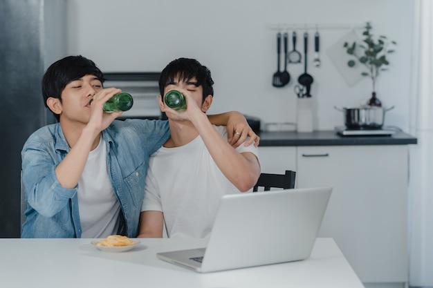 Le giovani coppie gay bevono la birra mentre utilizzano il computer portatile del computer a casa moderna. gli uomini asiatici di lgbtq si rilassano felici usando la tecnologia gioca insieme ai social media mentre sono seduti a tavola in cucina a casa.