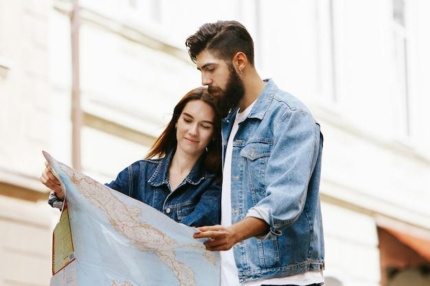 Le giovani coppie in vestiti dei jeans si leva in piedi con il touristc mappano da qualche parte nella vecchia città