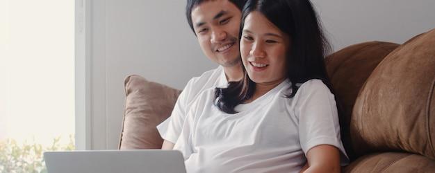 Le giovani coppie incinte asiatiche facendo uso del computer portatile cercano le informazioni di gravidanza. mamma e papà sentirsi felici sorridenti positivi e pacifici mentre si prendono cura del loro bambino sdraiato sul divano nel salotto di casa.