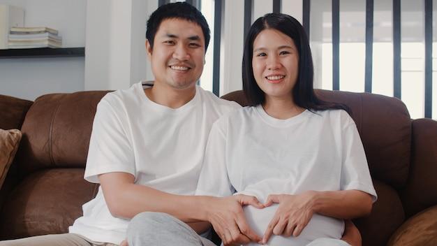 Le giovani coppie incinte dell'asiatico che fanno il cuore firmano la pancia della tenuta. mamma e papà sentirsi felici sorridenti pacifici mentre abbi cura del bambino, gravidanza sdraiata sul divano nel salotto di casa.