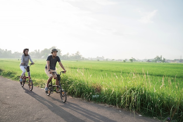 Le giovani coppie indossano i caschi per guidare bici pieghevoli nelle risaie