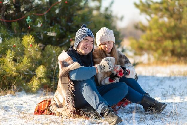 Le giovani coppie innamorate bevono una bevanda calda, seduti in inverno nella foresta, nascosto in caldo