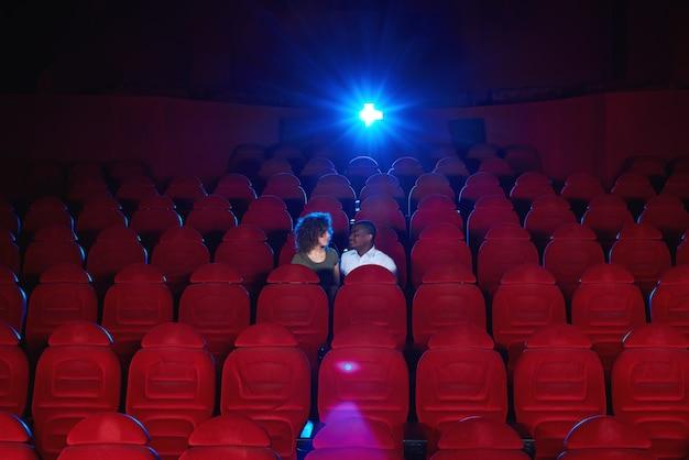 Le giovani coppie interrazziali che si siedono in un corridoio vuoto del cinema che guardano un film insieme copyspace amano il concetto romantico di attività di intrattenimento della data di anniversario di vip di romanticismo.