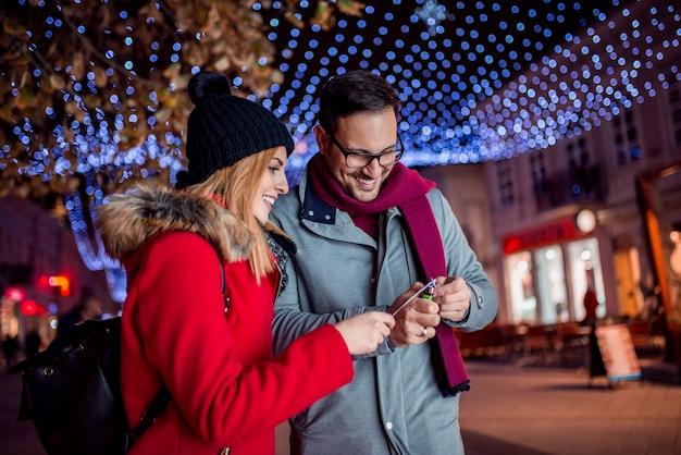 Le giovani coppie si divertono bruciando le luci di bengala nella via della città alla notte.