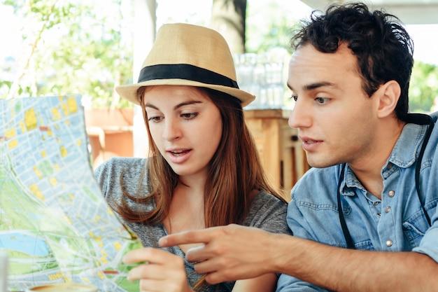 Le giovani coppie turistiche stanno guardando una mappa