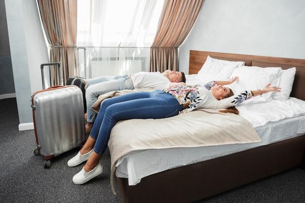 Le giovani coppie viaggiano insieme per il tempo libero della camera d'albergo