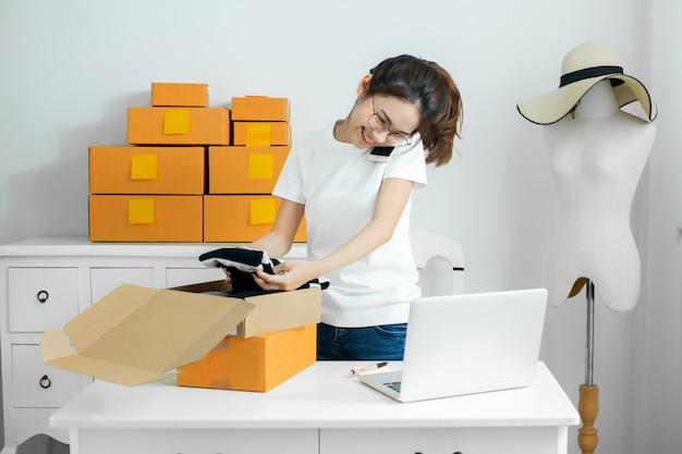 Le giovani donne acquistano il prodotto per gli ordini online e le confezionano nella scatola a casa sua.