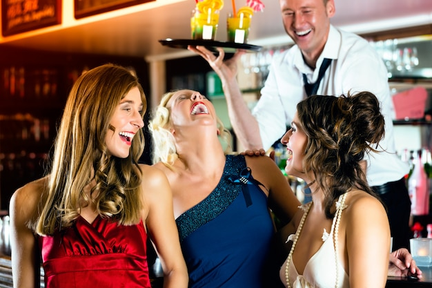 Le giovani donne al bar o al club si divertono e ridono, il barista serve cocktail