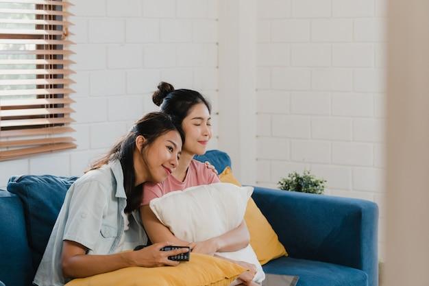 Le giovani donne asiatiche del lgbtq delle coppie asiatiche guardano la tv a casa