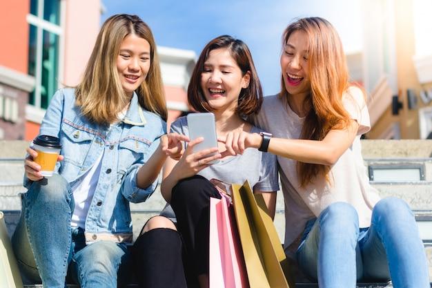 Le giovani donne asiatiche felici raggruppano lo stile di vita della città giocando e chiacchierando
