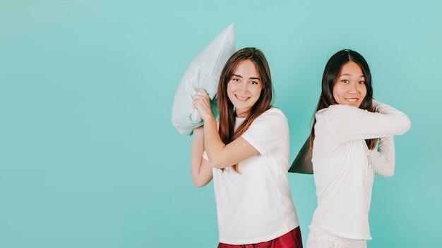 Le giovani donne che hanno cuscino combattono con la macchina fotografica