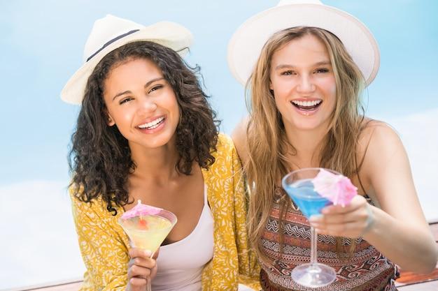 Le giovani donne che mangiano martini si avvicinano allo stagno