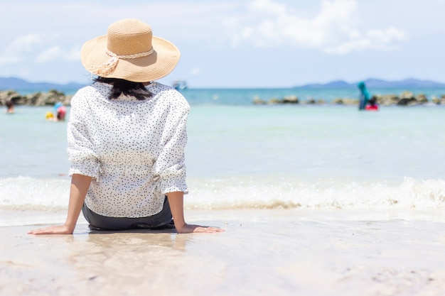 Le giovani donne che viaggiano si rilassano sulla spiaggia di estate