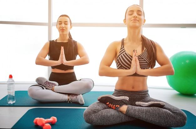 Le giovani donne concentrate e calme si siedono nella posa del loto e tengono le mani insieme.